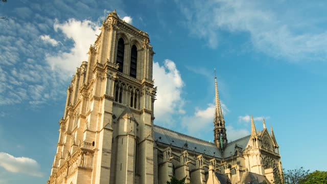 t/l zo pan down shot of notre dame in paris, france with clouds - notre dame de paris stock videos and b-roll footage