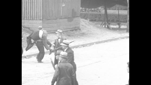 "down street as tear gas wafts during melee between white-arm banded deputies and steel mill picketers / group of deputies walks past sign ""steel... - tear gas stock videos & royalty-free footage"