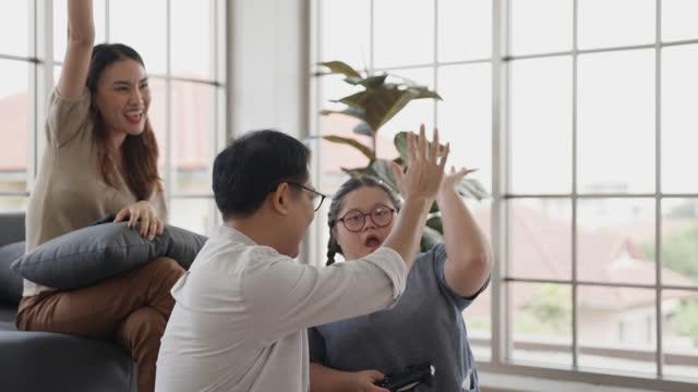 vídeos de stock, filmes e b-roll de uma garota asiática com síndrome de down jogando jogo de realidade virtual com o pai e muito feliz - menina