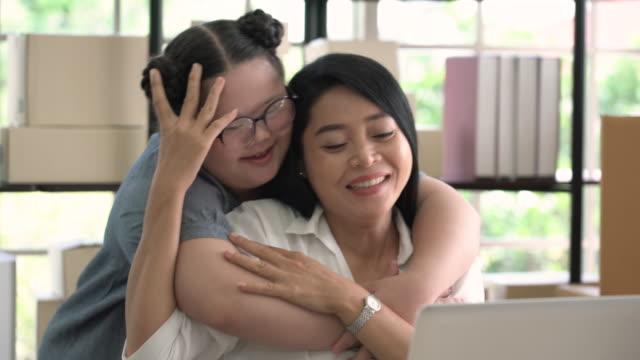 ダウン症の娘は後ろからラップトップを使用して彼女の母親を抱きしめる - 自閉症点の映像素材/bロール