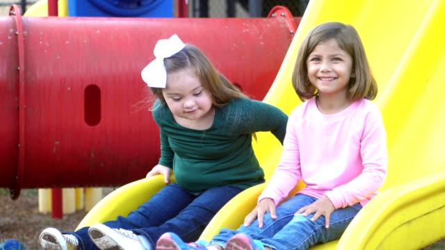 vídeos de stock, filmes e b-roll de garota de síndrome de down e amigo no slide de parque infantil - parque infantil