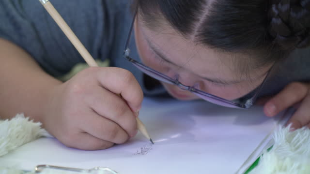 down syndrome girl drawing on paper - one teenage girl only stock videos & royalty-free footage