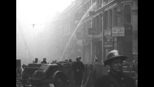 vídeos y material grabado en eventos de stock de down tower at st. bride's church with heavy smoke and rubble in foreground and buildings on either side / firefighters spraying water into destroyed... - el blitz