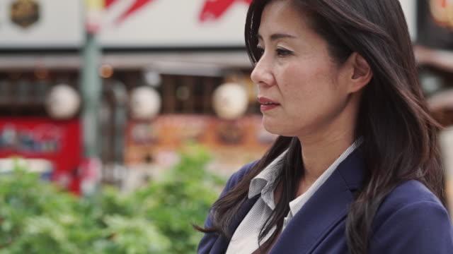 downcast woman in tokyo street - 心配する点の映像素材/bロール