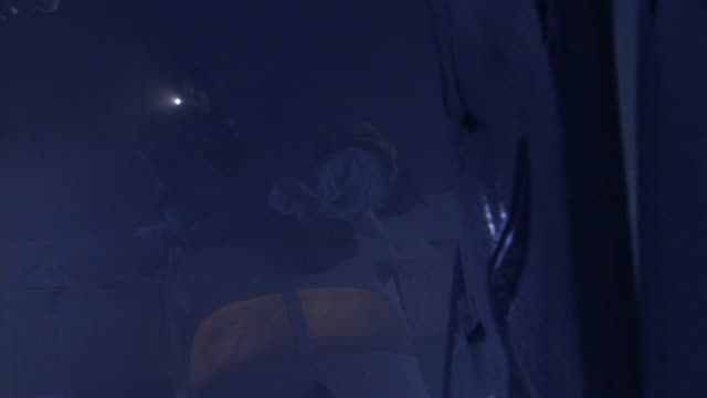 A downed pilot examines his surroundings with a flashlight.