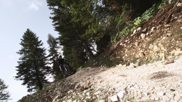 vídeos de stock, filmes e b-roll de hd câmera lenta: ciclista na ladeira pulando em trilhas irregulares - filme colagem