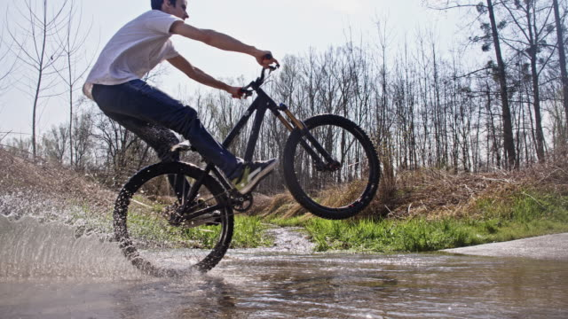 SLO MO Downhill biker performing wheelie through a puddle