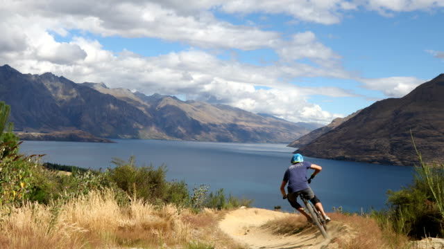 downhill mountain biker descends picturesque slope - new zealand stock videos & royalty-free footage