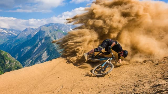 downhill mountain biker falling on dirt road, leaving a cloud of dust behind - fallimento video stock e b–roll