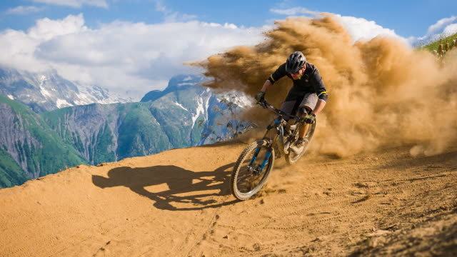 downhill mountain biker making a turn on dirt road, leaving a cloud of dust behind - bicycle trail outdoor sports stock videos & royalty-free footage