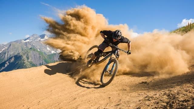 vidéos et rushes de cycliste de montagne de descente effectuant un virage sur le chemin de terre, laissant un nuage de poussière derrière, ralenti - faire du vélo tout terrain