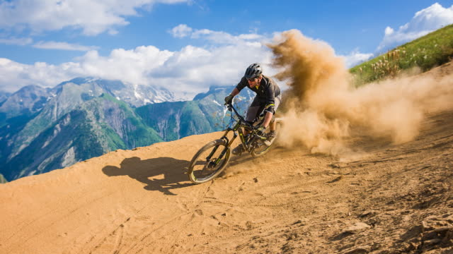downhill mountain biker making a turn on dusty dirt road on a sunny day - andare in mountain bike video stock e b–roll