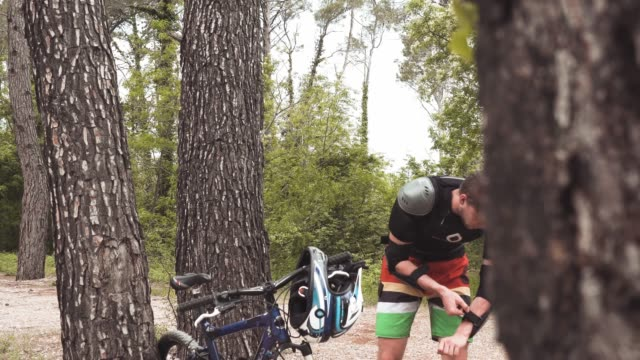 downhill mountain biker putting of his protective sportswear - crash helmet stock videos and b-roll footage