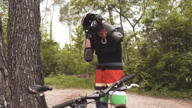 downhill mountainbiker seinen schutzhelm ablegen - sportschutzhelm stock-videos und b-roll-filmmaterial