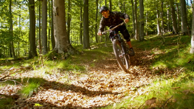 SLO MO Downhill mountain biker speeding through the forest