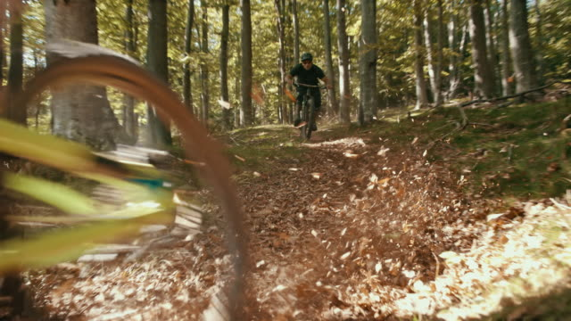 slo mo downhill mountain bikers carving through turn in a forest - mountain biking stock videos & royalty-free footage