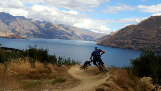 downhill mountain bikers descend picturesque slope - queenstown stock videos & royalty-free footage