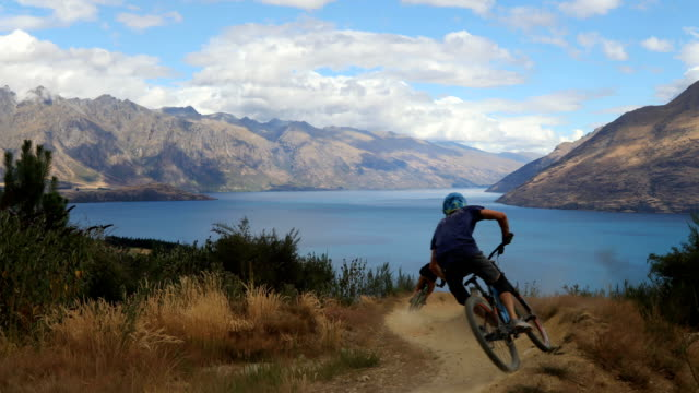 downhill mountain bikers descend picturesque slope - mountain bike stock videos & royalty-free footage
