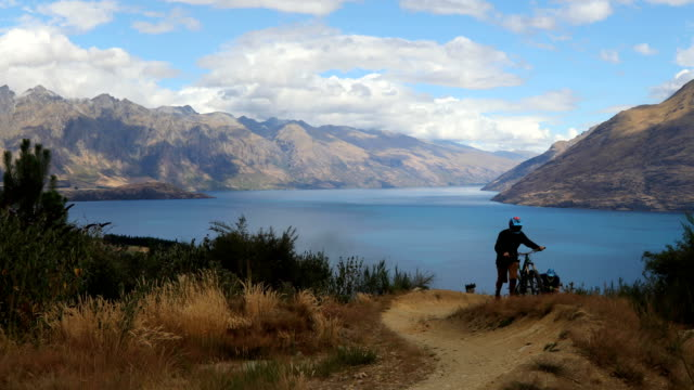 downhill mountain bikers push bikes up picturesque slope - queenstown stock videos & royalty-free footage