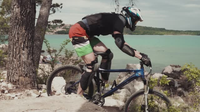stockvideo's en b-roll-footage met downhill mountainbiken aan zee - valhelm
