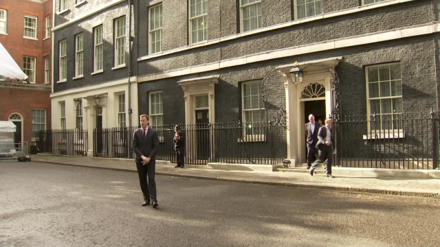 downing street and london eye; more of number 10 as reporter does piece to camera / number 10 door / workers arriving at number 10 with trolleys /... - ランベス点の映像素材/bロール