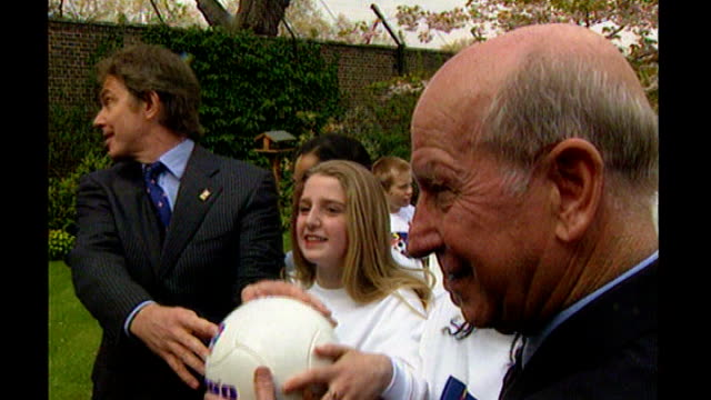 downing street: ext tony blair mp with sir bobby charlton and children in garden posing with football as part of bid to win the 2006 world cup for... - bid stock videos & royalty-free footage