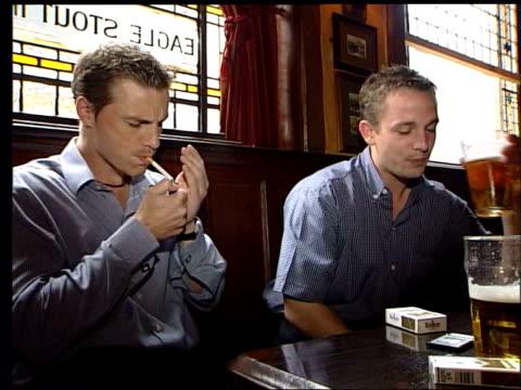 night formula one head bernie ecclestone along to no10 lib int ms smoker lighting up in pub cs woman smoking cigarette cs man smoking cigarette cs... - bernie ecclestone stock videos & royalty-free footage