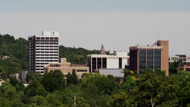 downtown buildings protrude from the trees forming the fayetteville ar skyline - arkansas stock videos & royalty-free footage