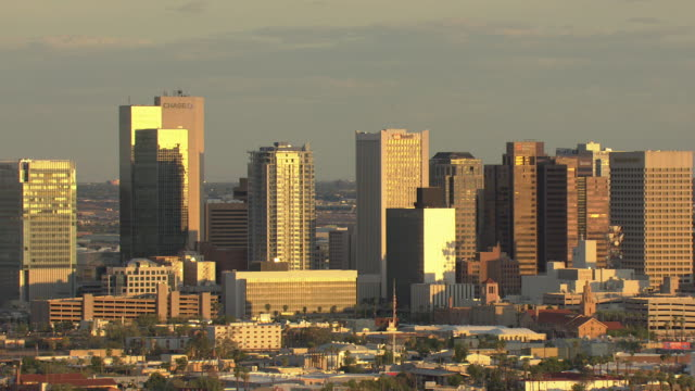 WS AERIAL Downtown buildings with bright sunlight reflecting / Phoenix, Arizona, United States