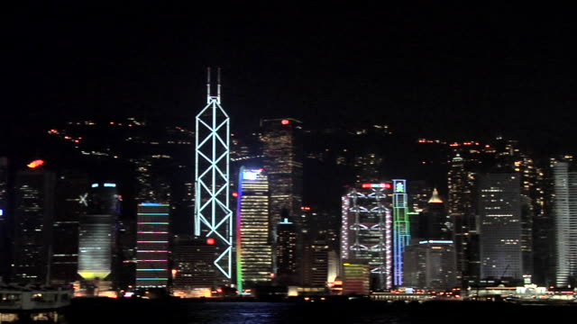 ws pan downtown buildings with international finance centre illuminated at night across victoria harbor / hong kong, china - central district hong kong stock videos and b-roll footage