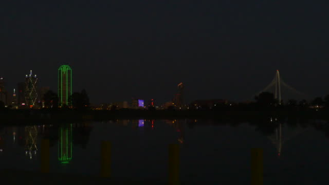 WS Downtown Dallas, Texas skyline at night, buildings lit up, reflecting in Trammell Crow Lake