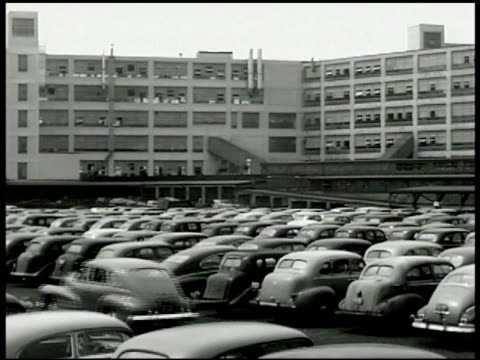 vidéos et rushes de downtown detroit ext automotive factory w/ large filled parking lot int factory w/ car tops being mechanically placed on conveyor cars on assembly... - michigan