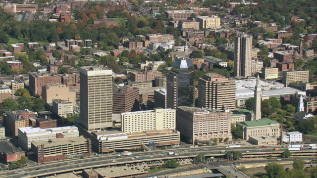 AERIAL Downtown high rises and freeway, and Springfield Armory in parkland with autumn foliage beyond / Springfield, Massachusetts, United States
