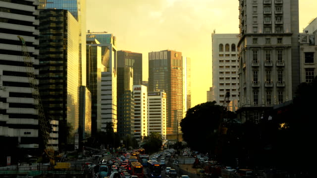downtown jakarta business district city scene at sunset with flowing traffic 4k video - jakarta stock videos & royalty-free footage