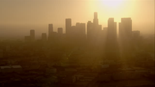 aerial downtown los angeles against sun, california, usa - smog video stock e b–roll
