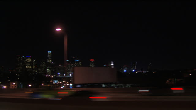 Downtown Los Angeles at night, seen from freeway; passenger POV