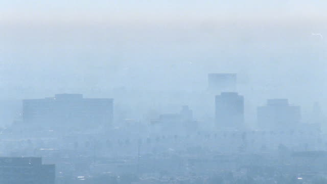 vidéos et rushes de downtown los angeles cluster of high-rises blanketed in thick smog, fog, time of day indeterminate. note: fingerprints on lens. - smog