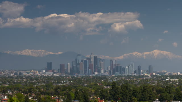 downtown los angeles skyline in winter with snow covered mountain range. - tilt down stock videos & royalty-free footage