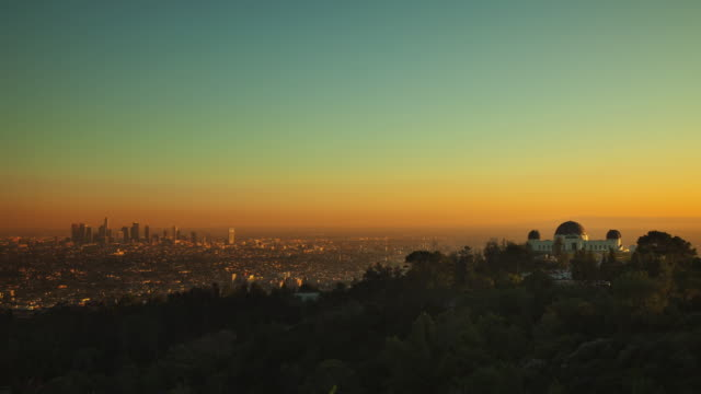 t/l ws ha downtown los angeles with griffith park observatory in foreground, day to night / california, usa - hill stock videos & royalty-free footage