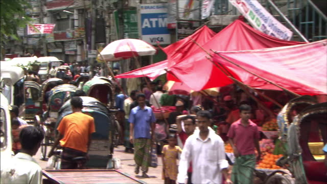 Miscellaneous Shots A line of roadside stalls People and rickshaws coming and going Pan Right