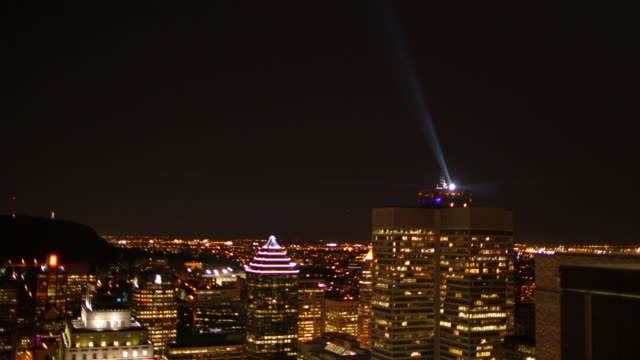 vidéos et rushes de downtown montreal at night with rotating spotlight - montreal
