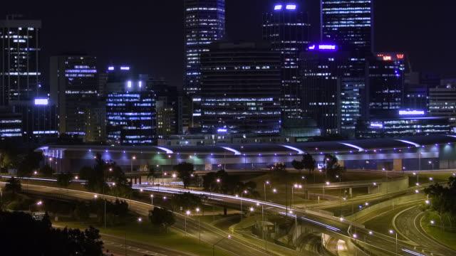T/L WS PAN TD MS Downtown Perth and traffic zipping along Kwinana Freeway in night / Perth, Western Australia, Australia