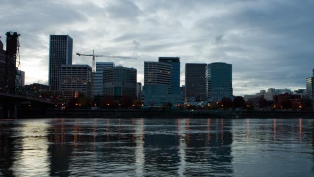 T/L WS PAN Downtown Portland skyline seen across Willamette River, dusk to night / Oregon, USA