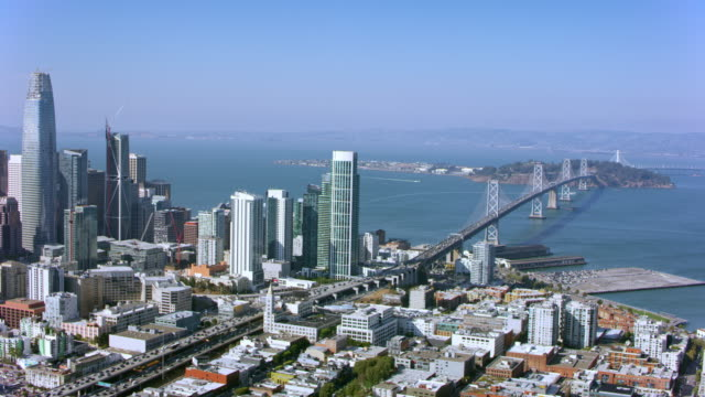 aerial downtown san francisco and the bay bridge on a sunny day - san francisco oakland bay bridge stock videos and b-roll footage