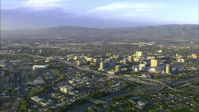 hd aerial ** xws downtown san jose cityscape low amp highrise buildings highways hp pavilion arena top frame mountains distant bg ca central business... - san jose california stock videos & royalty-free footage