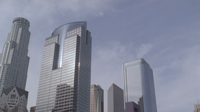 la downtown skyline against partly cloudy sky, with socal gas center and u.s. bank tower / los angeles, california, united states - us bank tower stock videos & royalty-free footage