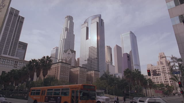 LA Downtown skyline against partly cloudy sky, with SoCal Gas Center and U.S. Bank Tower looming over pedestrians, traffic, and smaller buildings / Los Angeles, California, United States