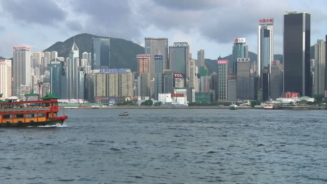 vídeos de stock, filmes e b-roll de ws downtown skyline with ferry crossing in foreground / hong kong, china - 2009