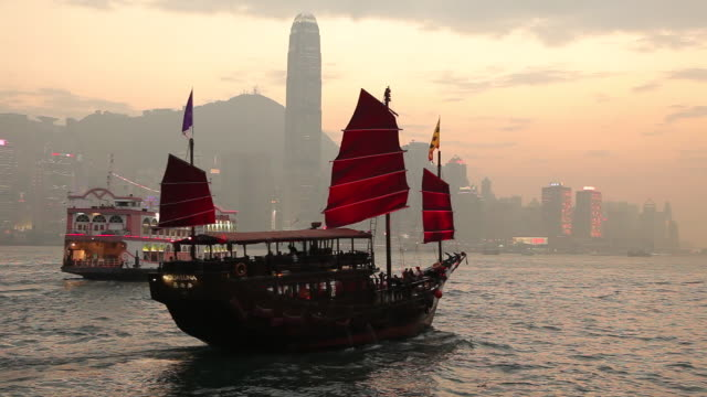 vidéos et rushes de ws downtown skyline with junk ship in harbor / hong kong, china - jonque