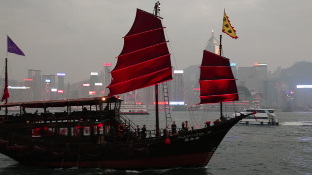 ws downtown skyline with junk ship in harbor / hong kong, china - dschunke stock-videos und b-roll-filmmaterial